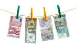 Different currency banknotes hanging on clothesline isolated on white background with clipping path